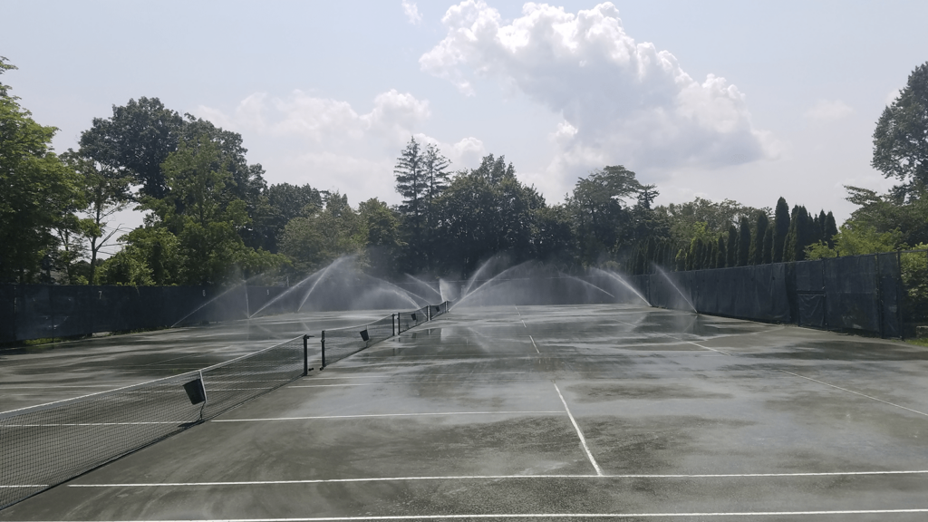 sprinkler on clay tennis courts at Quaker Ridge