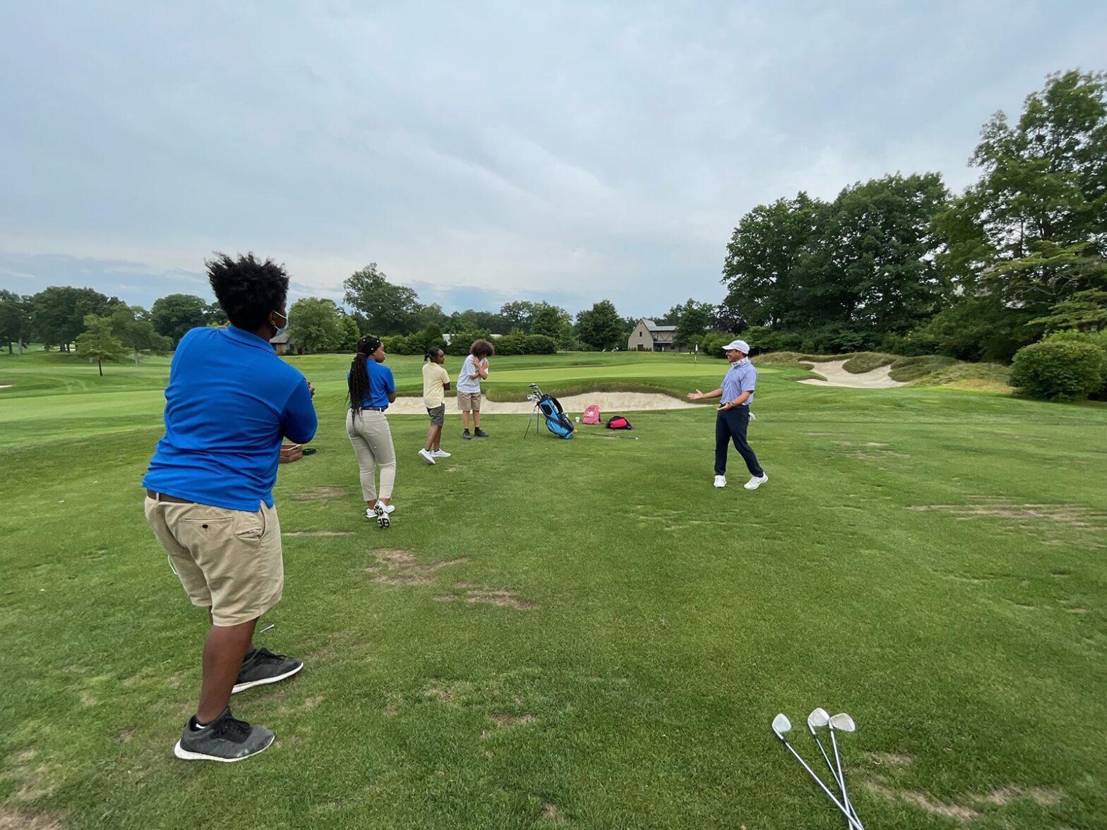 Quaker Ridge fellows during a golf lesson